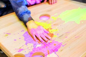 A hand touches a table which has colourful splashes of light, similar to ink splatters, projected on to it.